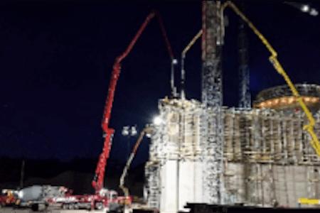 Vue de nuit de silos de clinker d'une usine de production de ciment