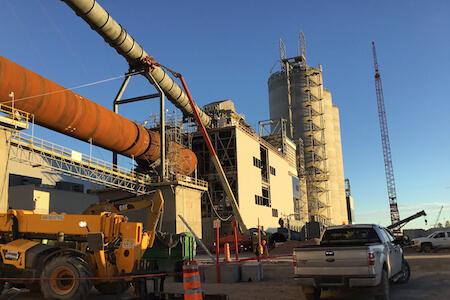 Vue d'une grue sur le site d'une usine de production de ciment