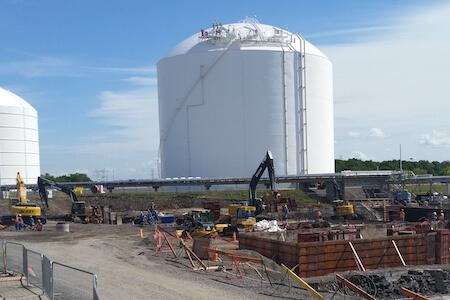 Vue d'un chantier de construction avec grue et silos en arrière-scène