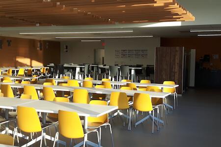 Vue des tables et des chaises dans une cafétéria située dans une tour à bureaux