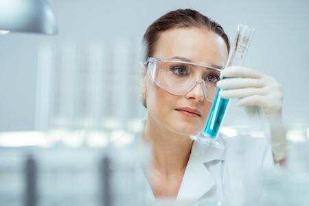 Microbiologiste portant des lunettes de protection analysant le contenu d'une éprouvette